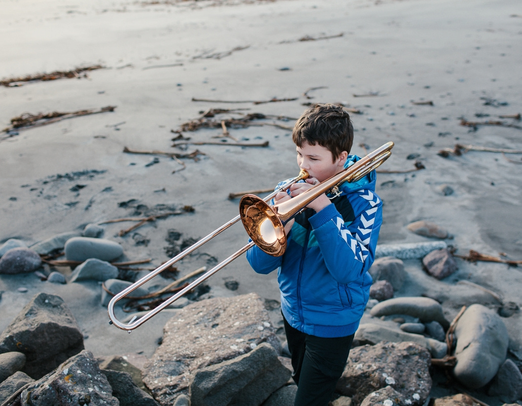 Simún Jacobsen playing trombone on the beach of Sandavágur, Faroe Islands. March 2016.